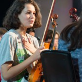 Young violinist holding instrument before concert