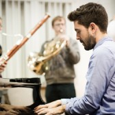 Young man playing piano with French Horn player in background